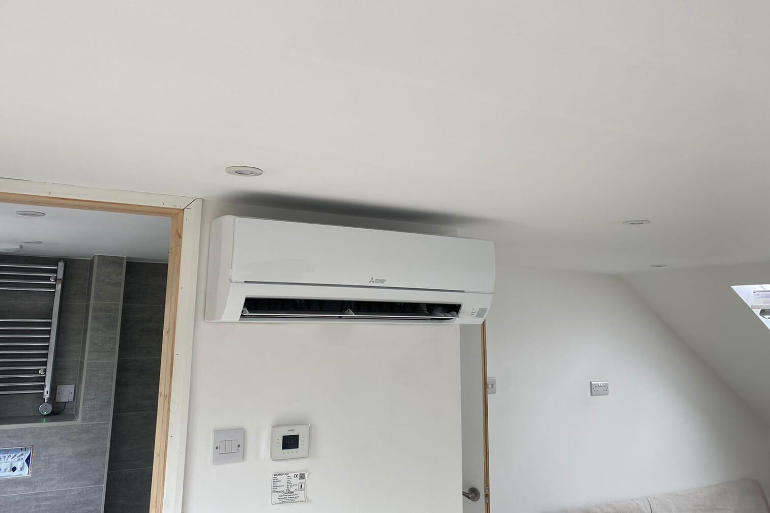 Littlehampton, West Sussex loft conversion with white Mitsubishi Electric wall-mounted air con unit inside by bathroom SubCoolFM