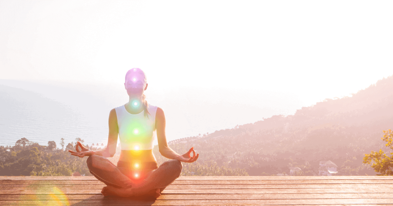Woman sitting in meditation with lit up chakras