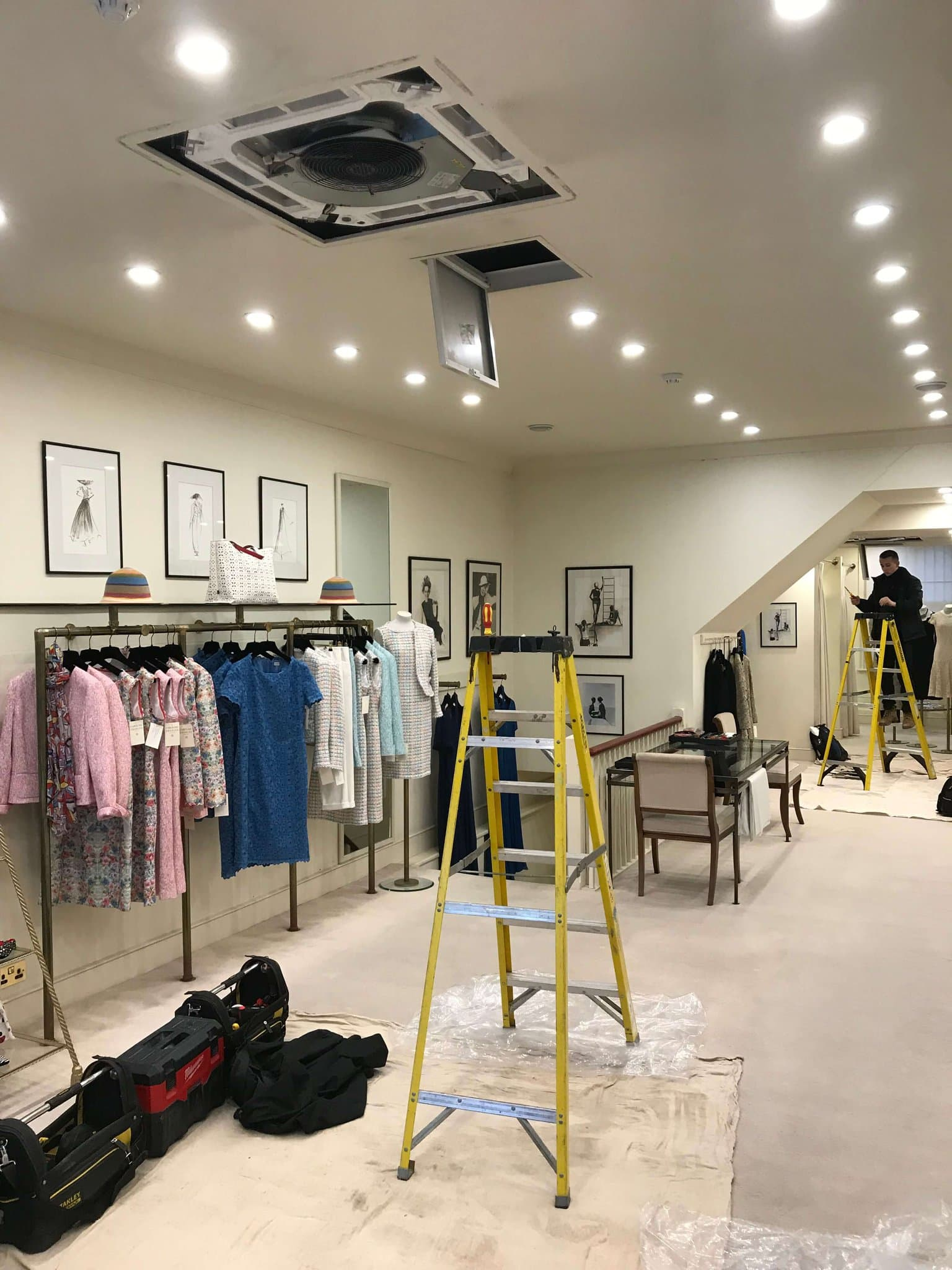 A ceiling air conditioning unit being installed in a fashion retail store