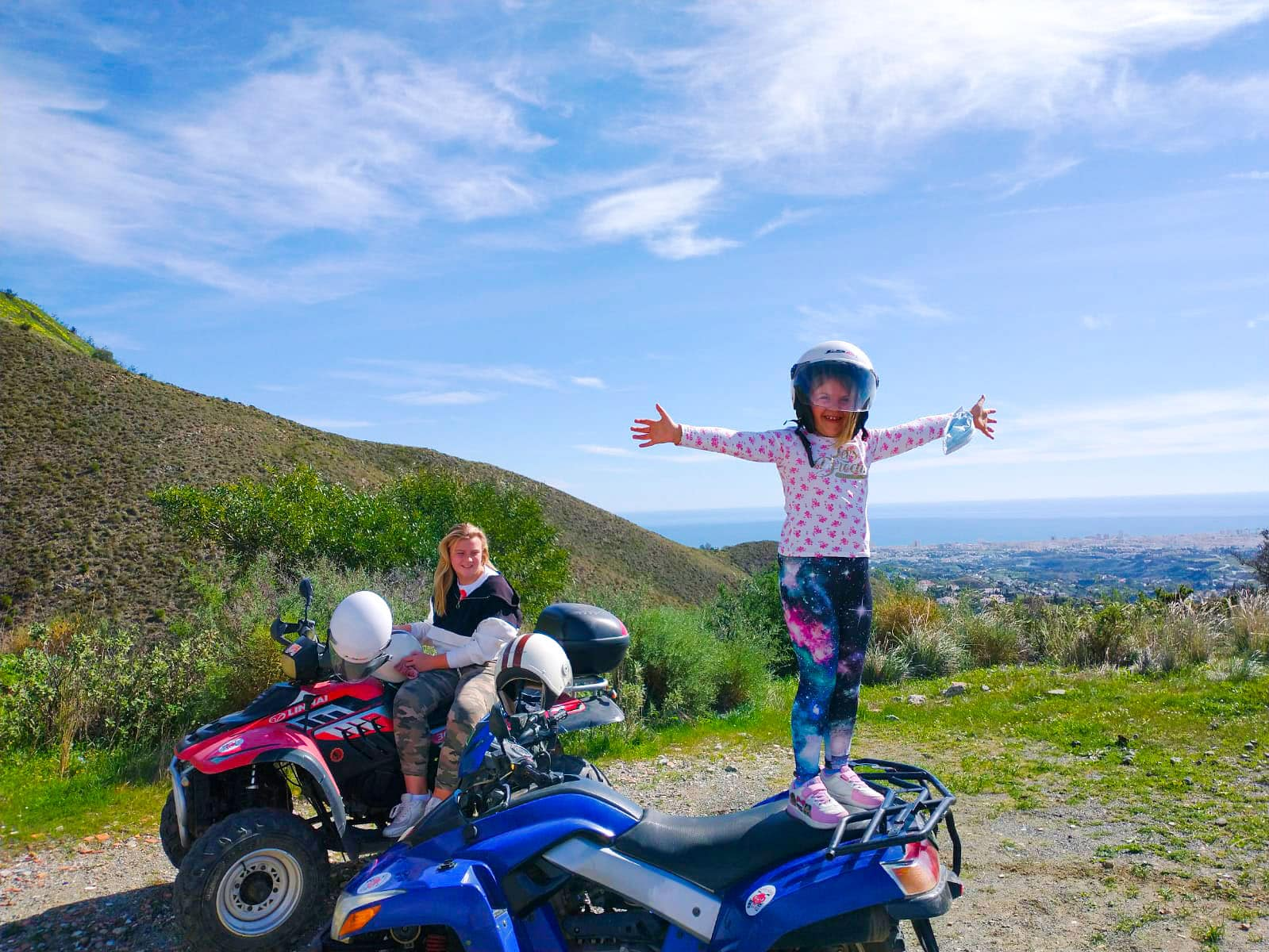 a young girls standing on a bike with arms wide spread, an older sister sitting on another bike laughing