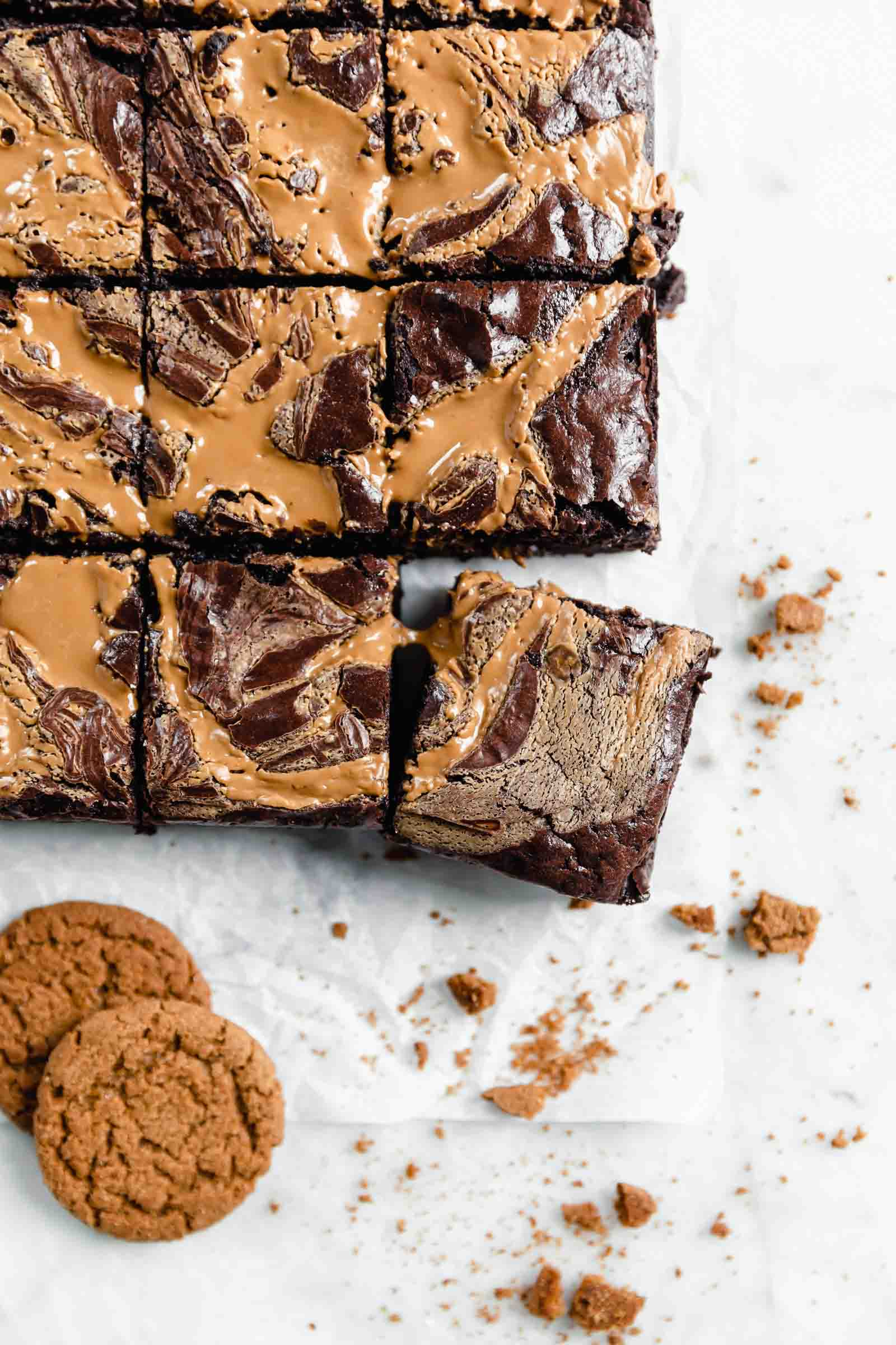 cookie butter swirled brownies on parchment paper with cookie crumbs