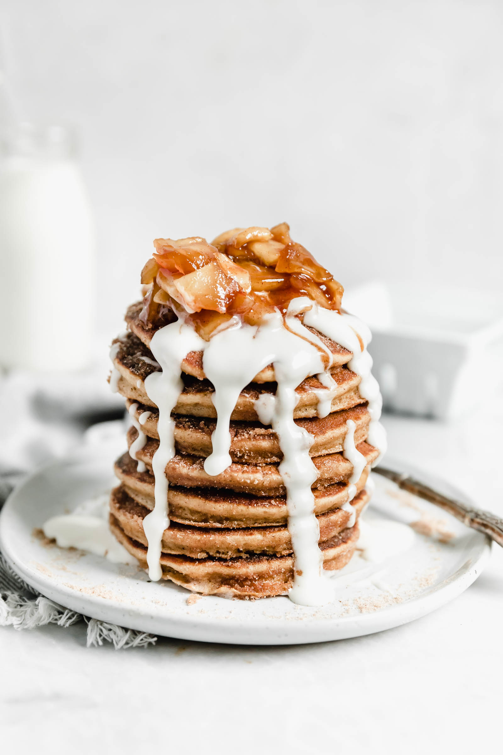 stack of apple cider donut pancakes topped with icing and cooked apples