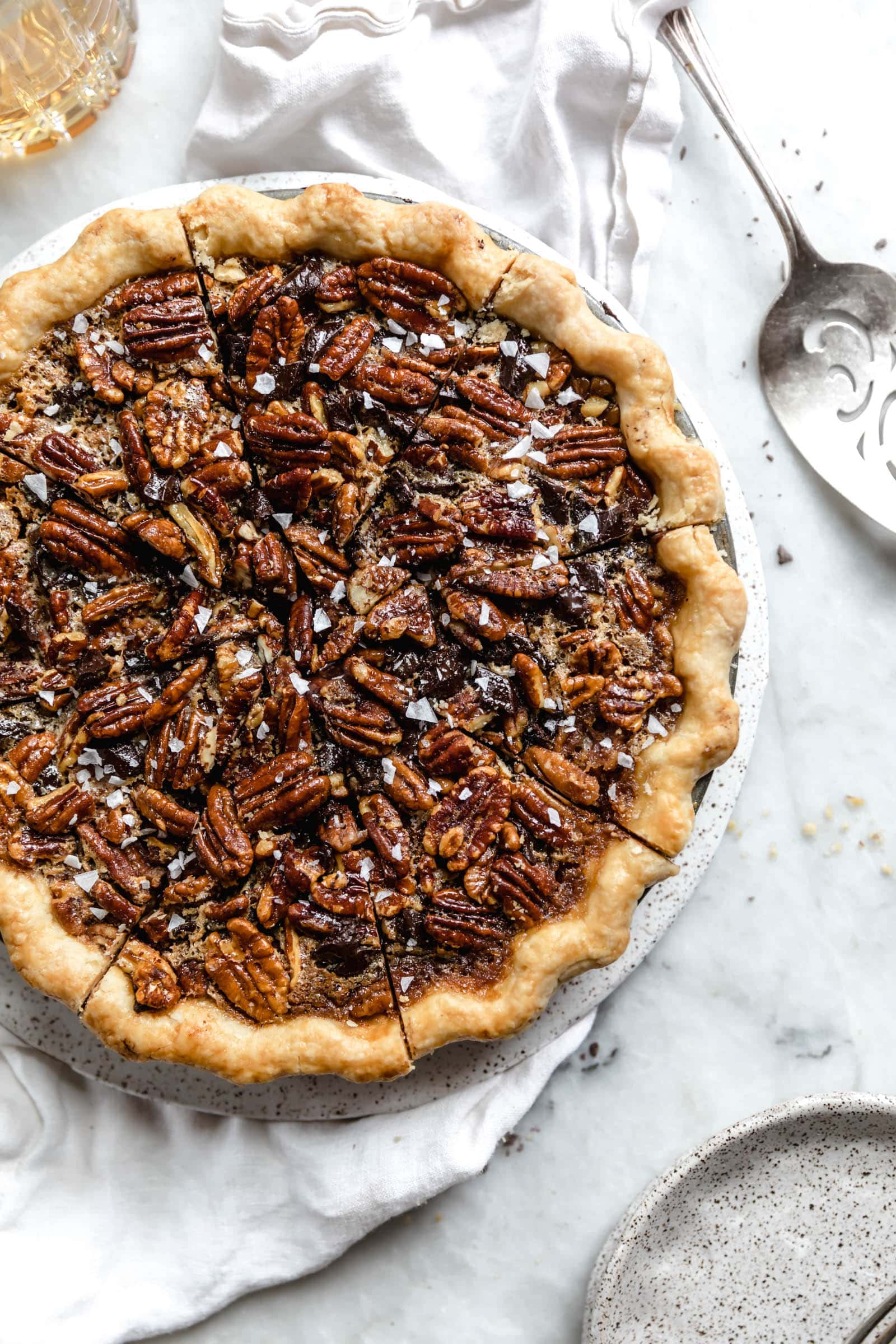overhead shot of bourbon chocolate pecan pie with pie cutter