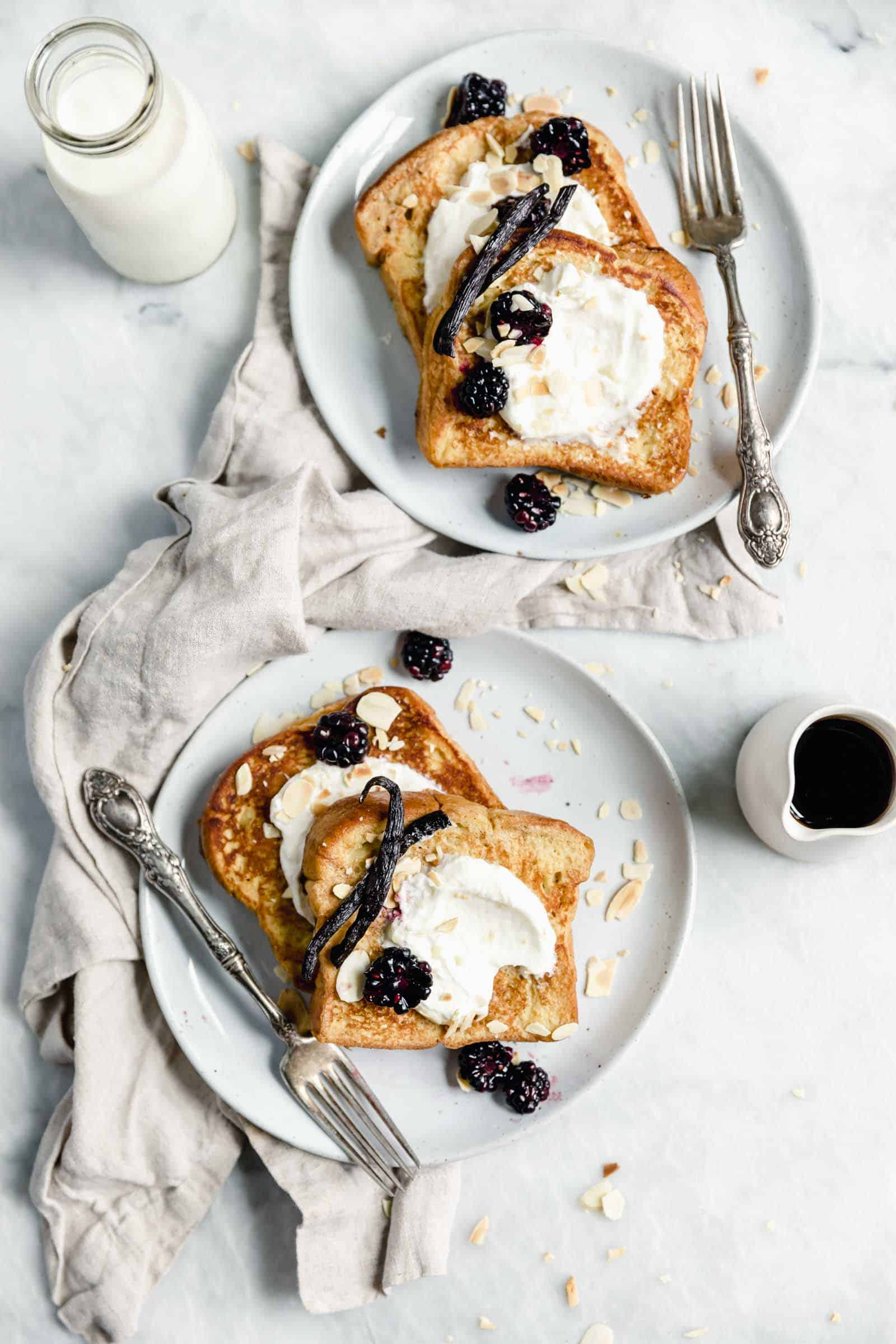 overhead shot of two plates of french toast with whipped cream and berries