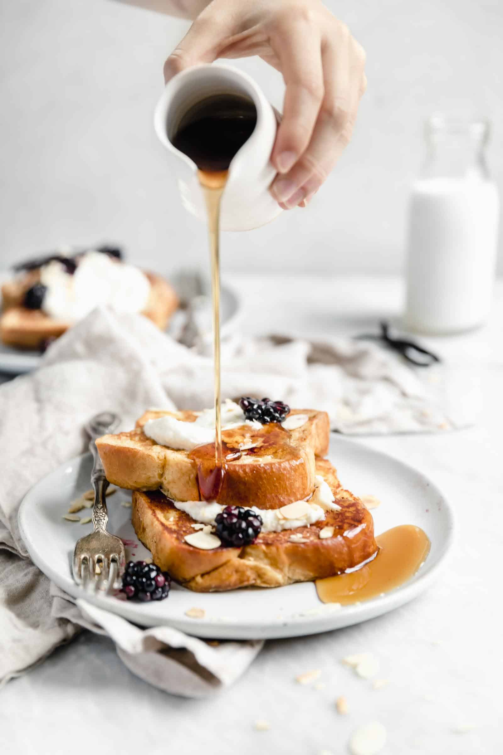 bourbon vanilla french toast being drizzled with maple syurp