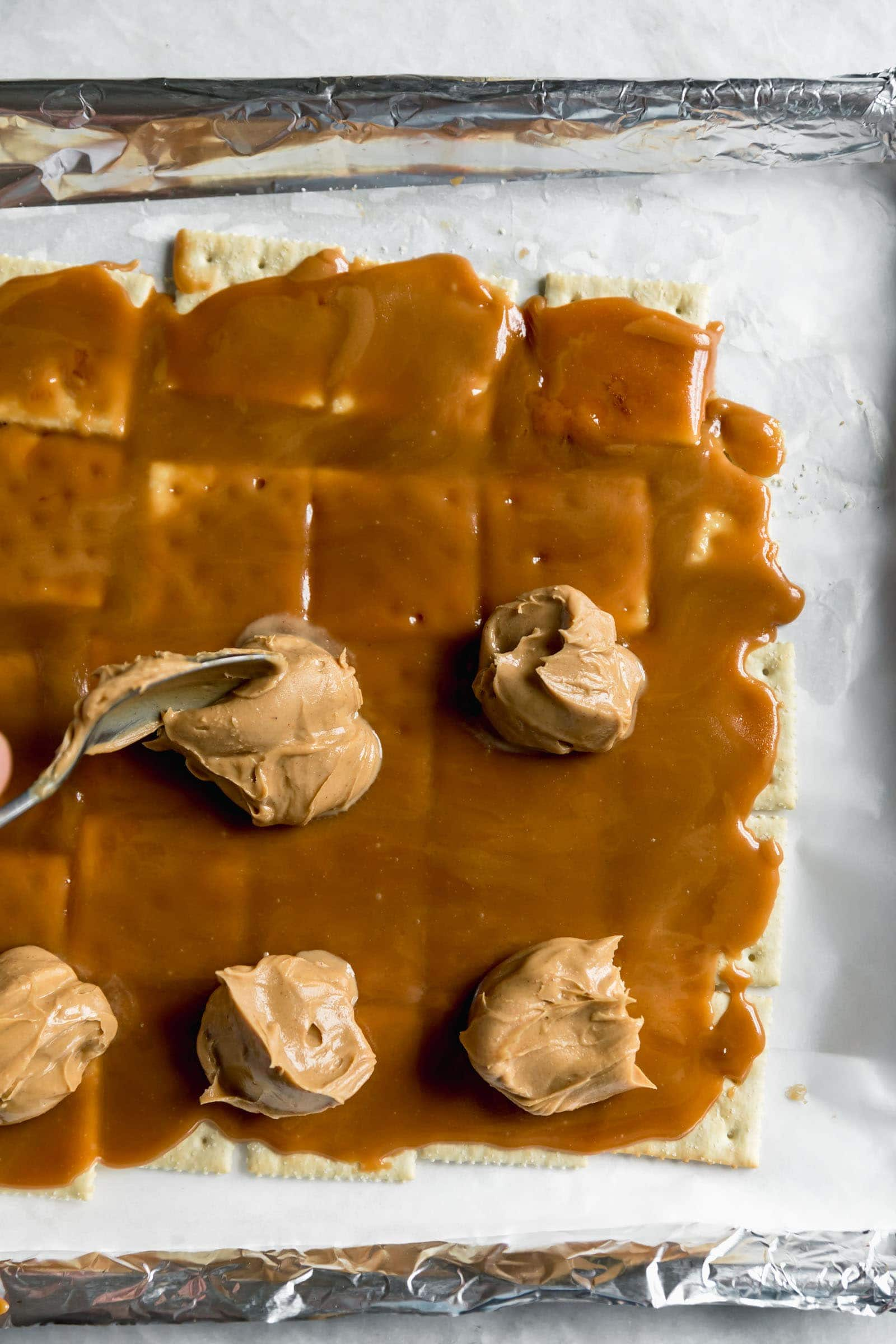 peanut butter dropped by spoonful on saltines