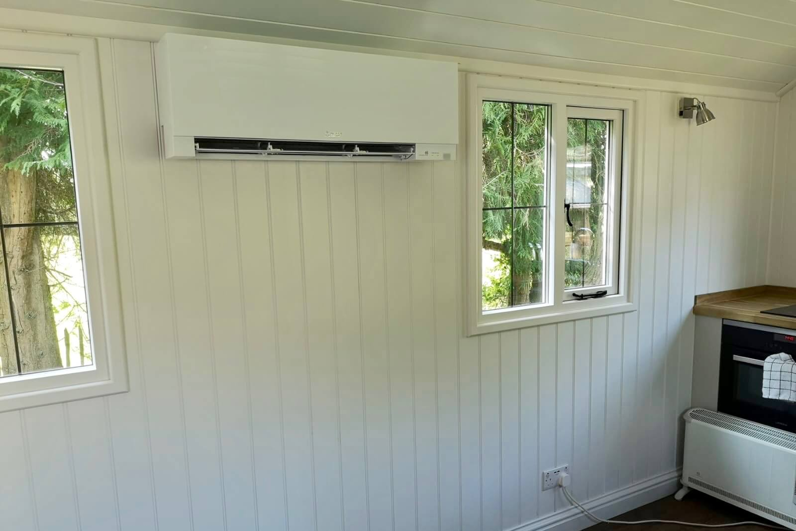 White mitsubishi air conditioning wall mounted unit fitted inside shepherds hut SubCool FM