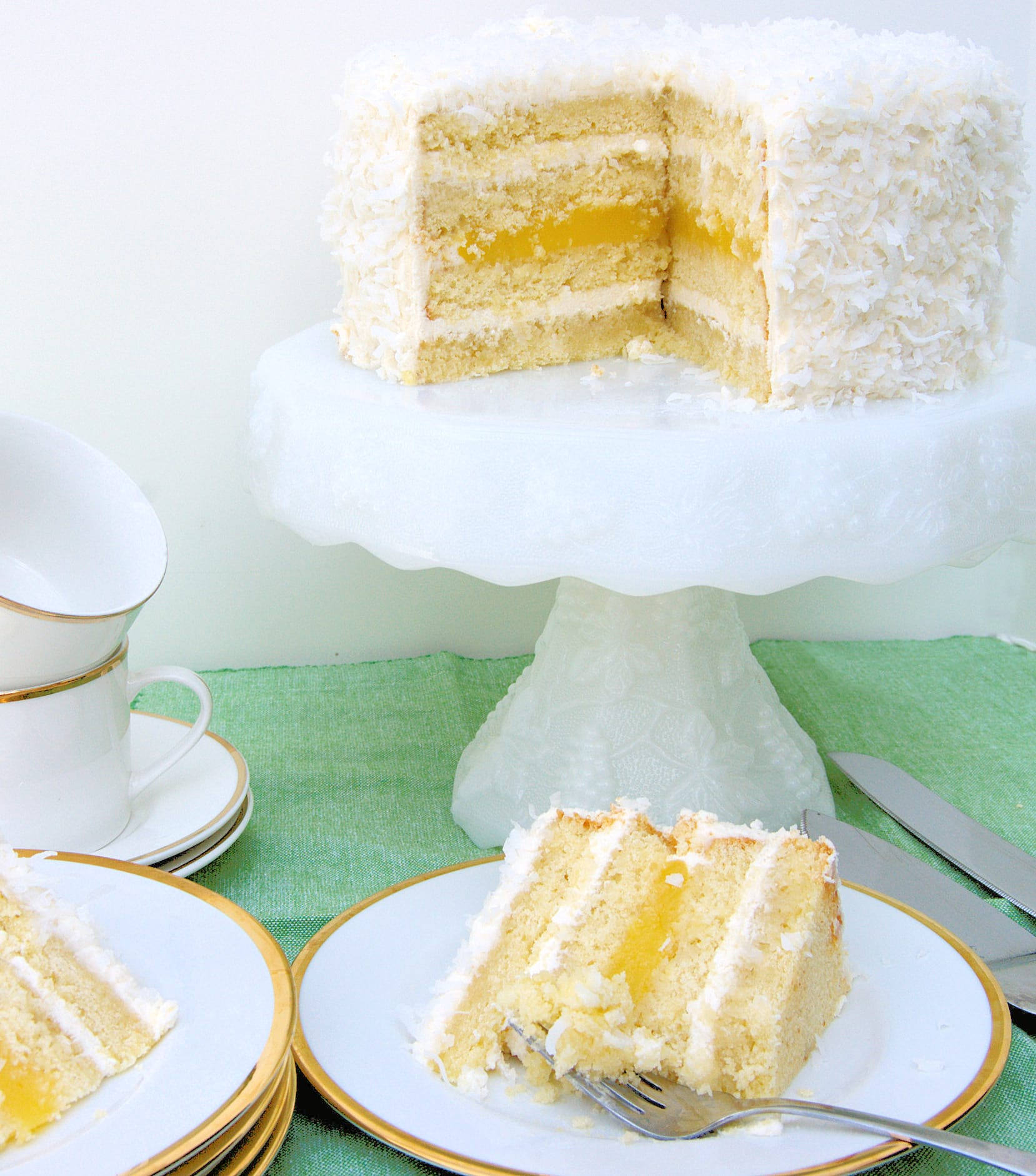 a sliced coconut passion fruit cake on a cake stand with a slice on a plate