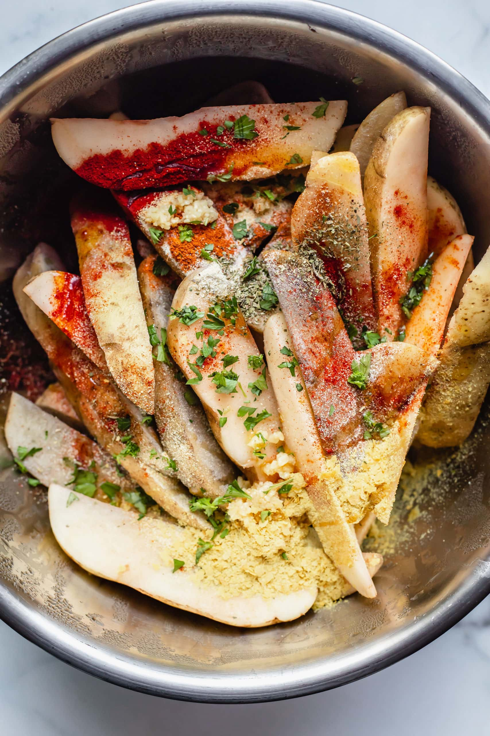Seasoned potato fries in a mixing bowl