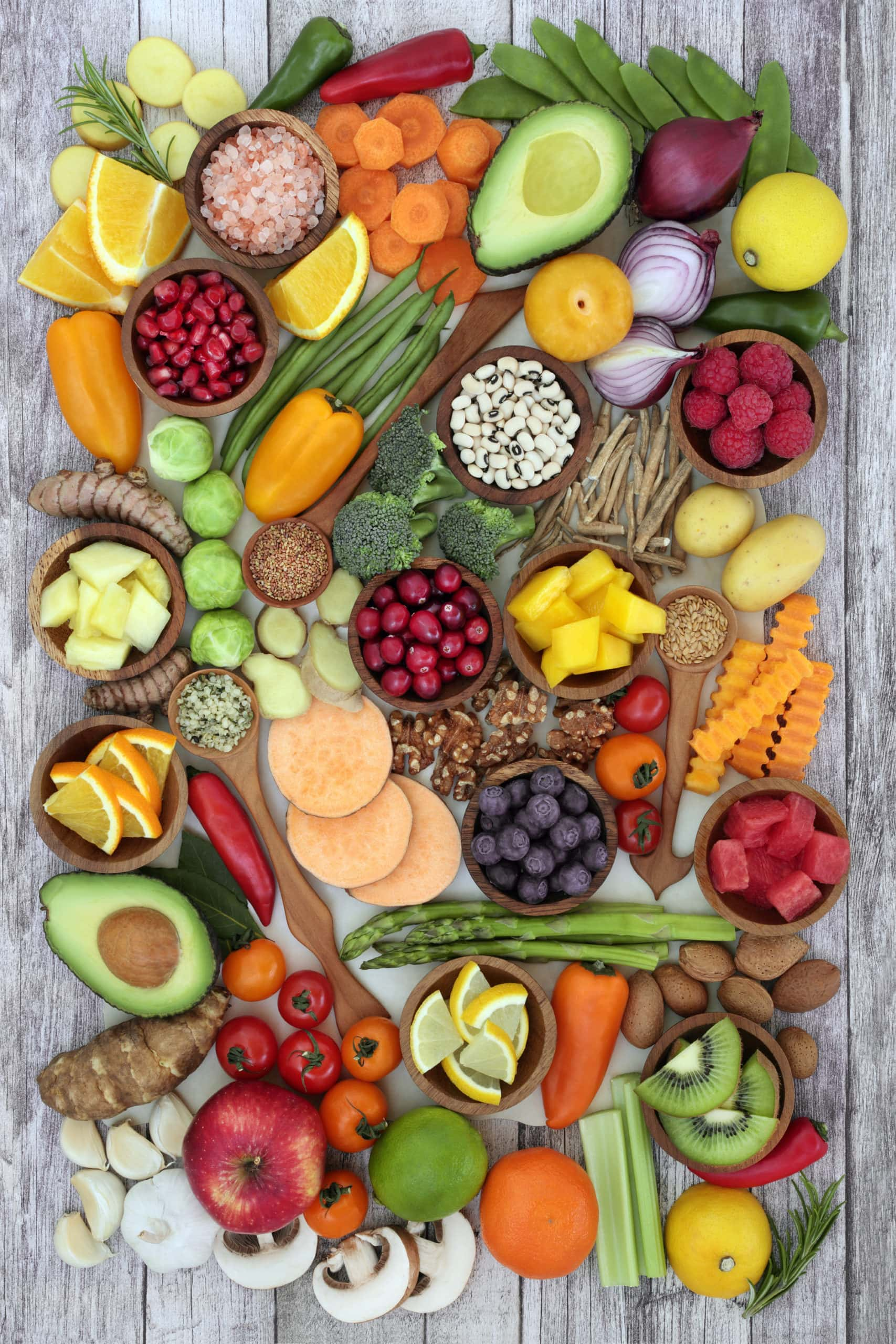 an assortment of fruits, vegetables, and grains, spread across a grey background