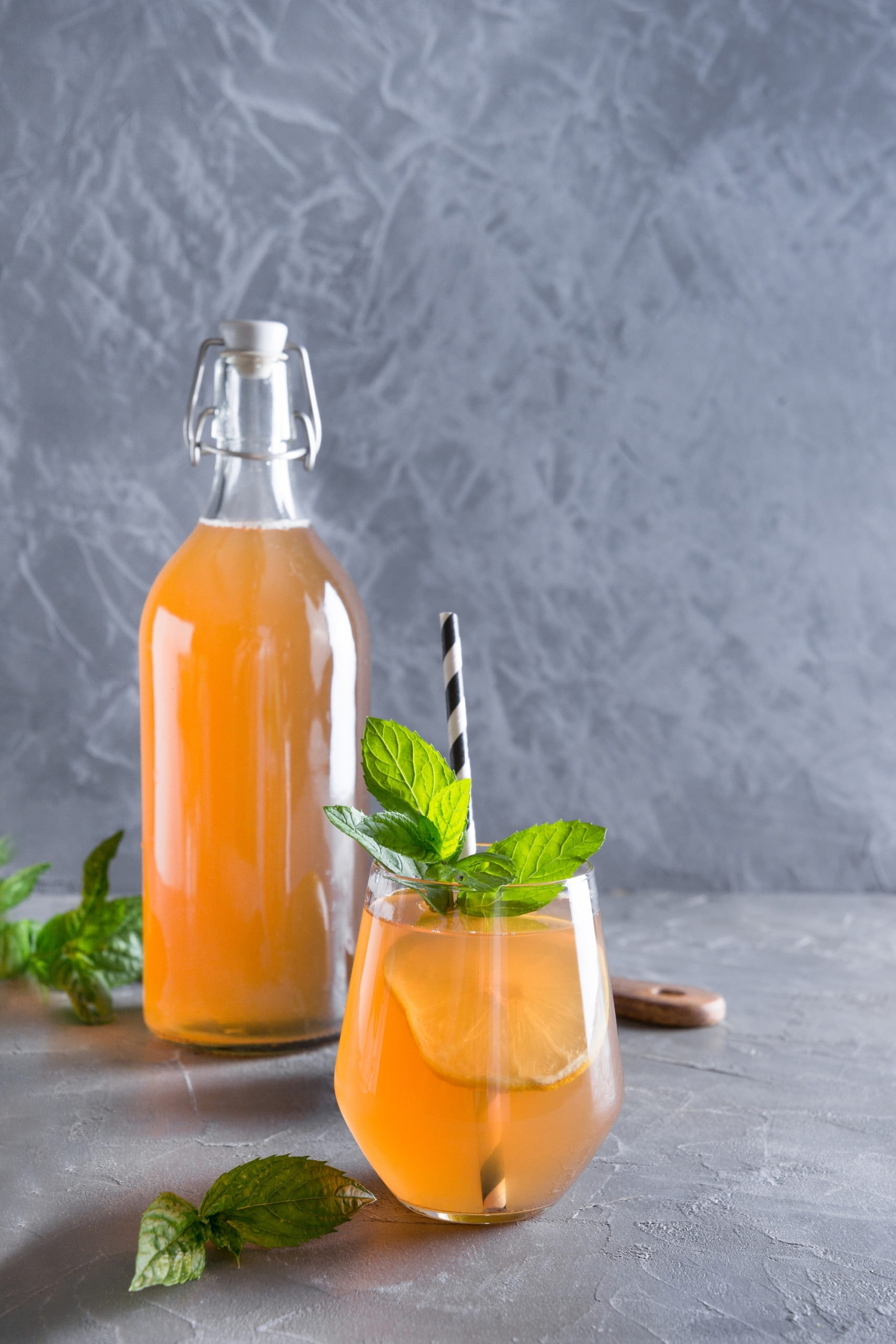 homemade kombucha in a bottle and a glass garnished with lemon, mint, and a black and white straw