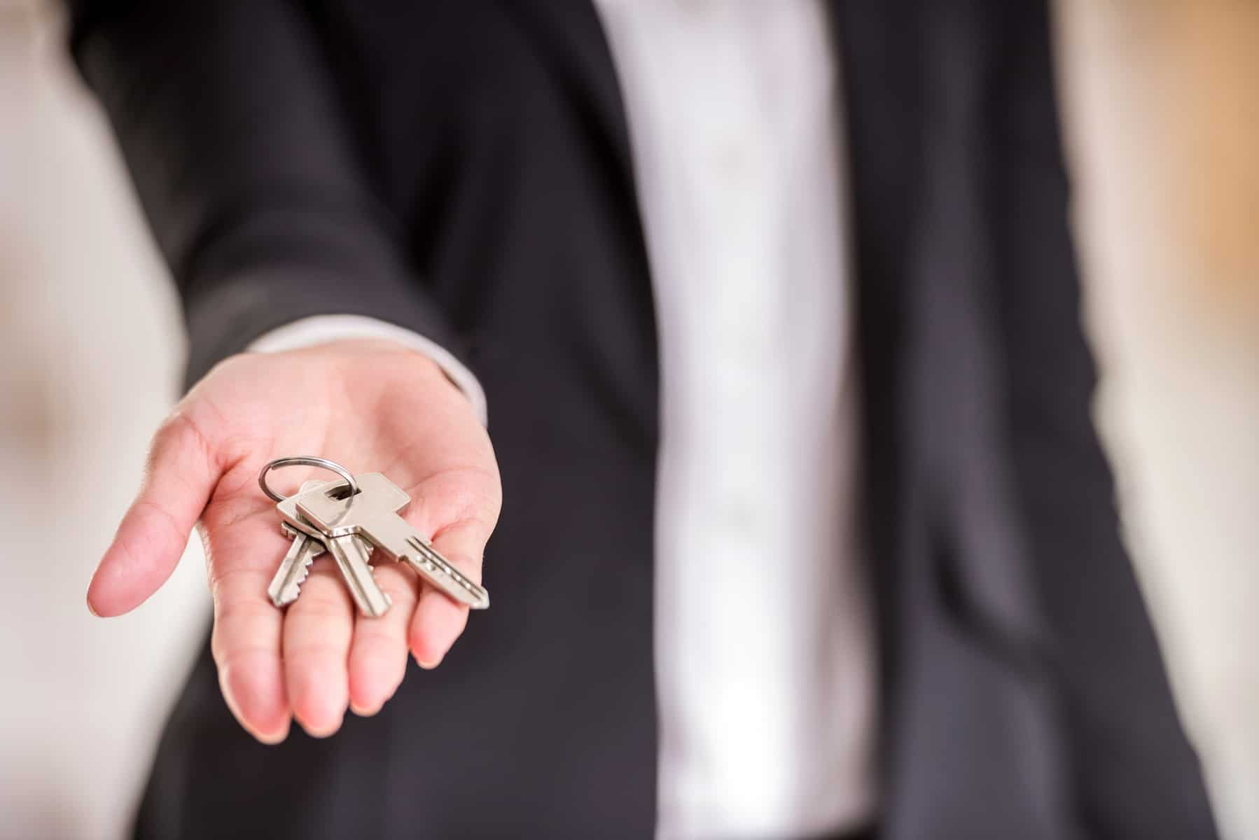Close-up of hand of realtor woman is holding key.
