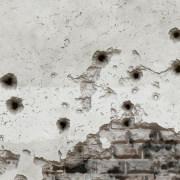 A wall marked with bullet holes