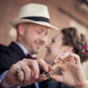 Eheringe im Vordergrund mit lachendem Brautpaar im Hintergrund