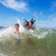 Kinder haben viel Spass beim baden mit großen Wellen