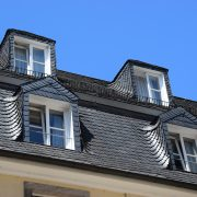 Ein Schieferdach mit Glasfenstern vor dem blauen Himmel.
