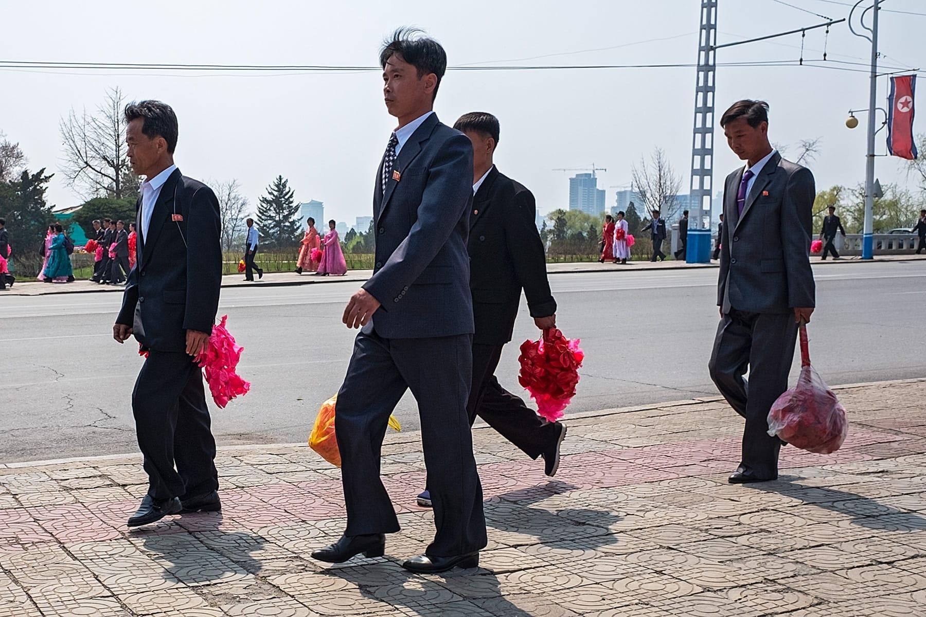 Vorübergehende Menschen mit roten Puscheln in der Hand