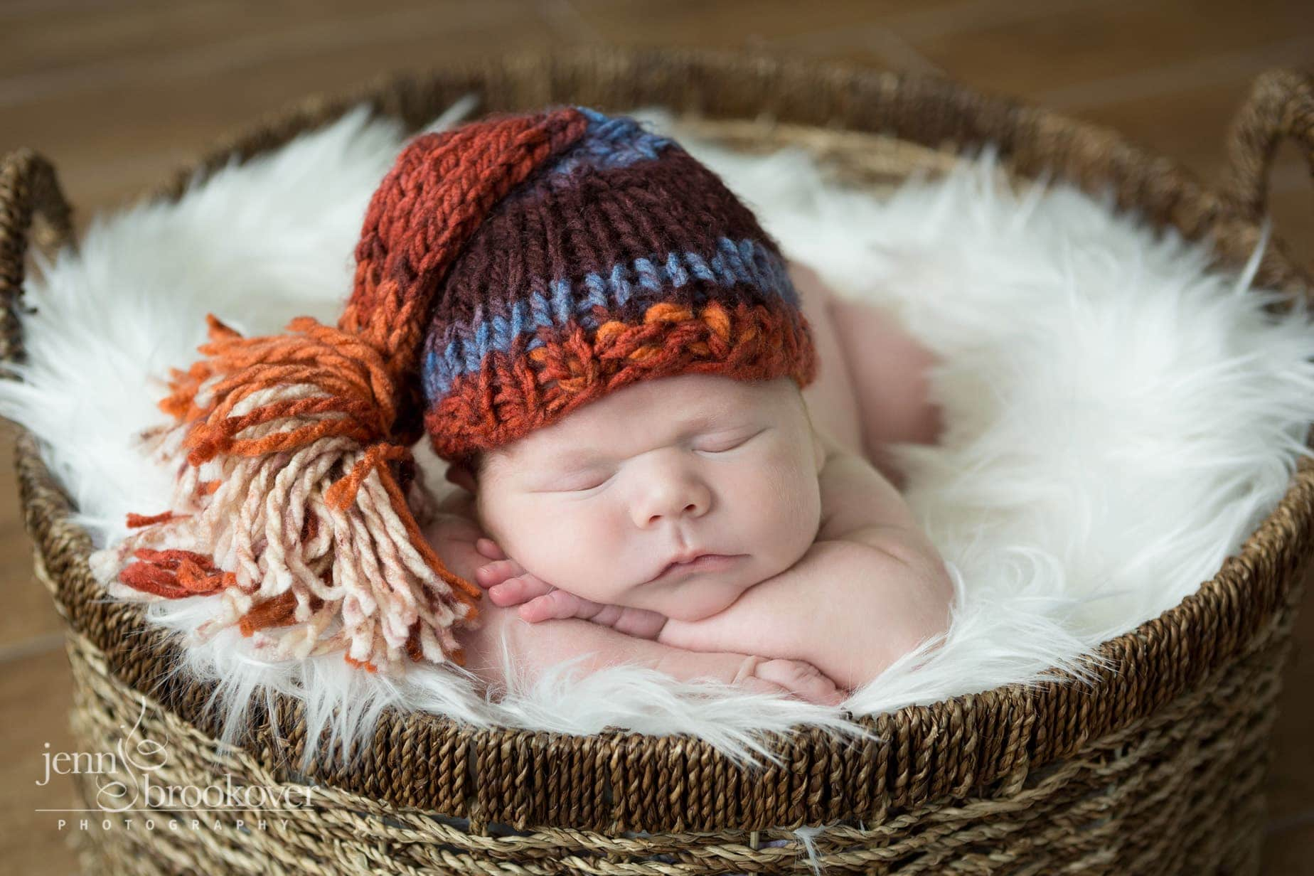 close up of newborn boy in knitted cap snuggling on fur during photo session
