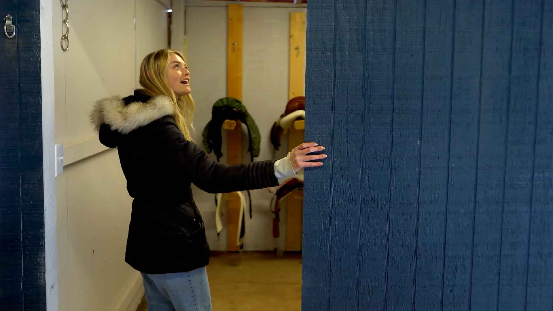 Willow Hand entering the tack room of her horse barn.