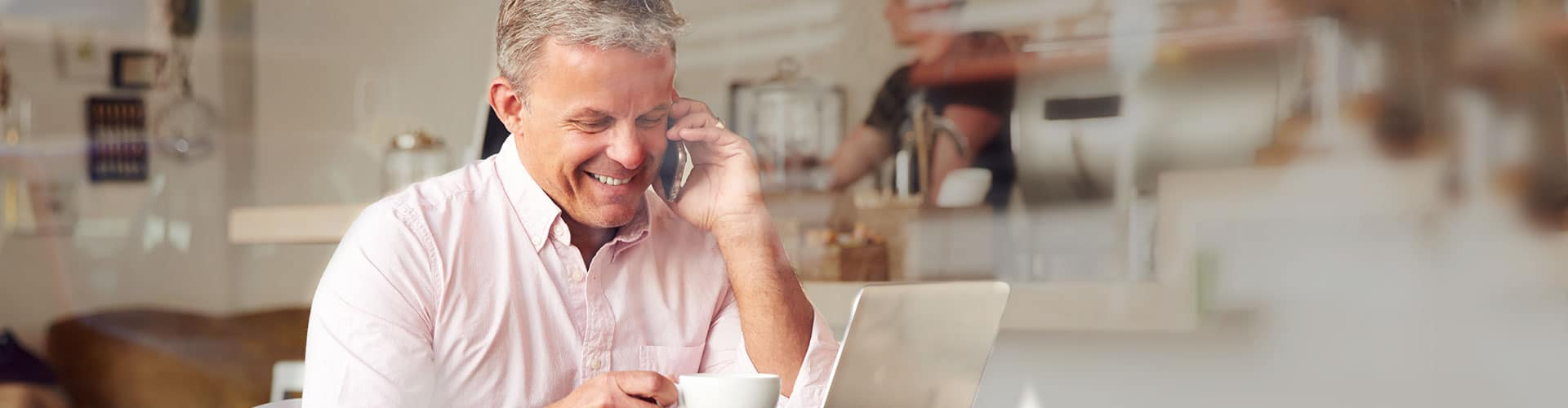 man talking on phone while looking at computer