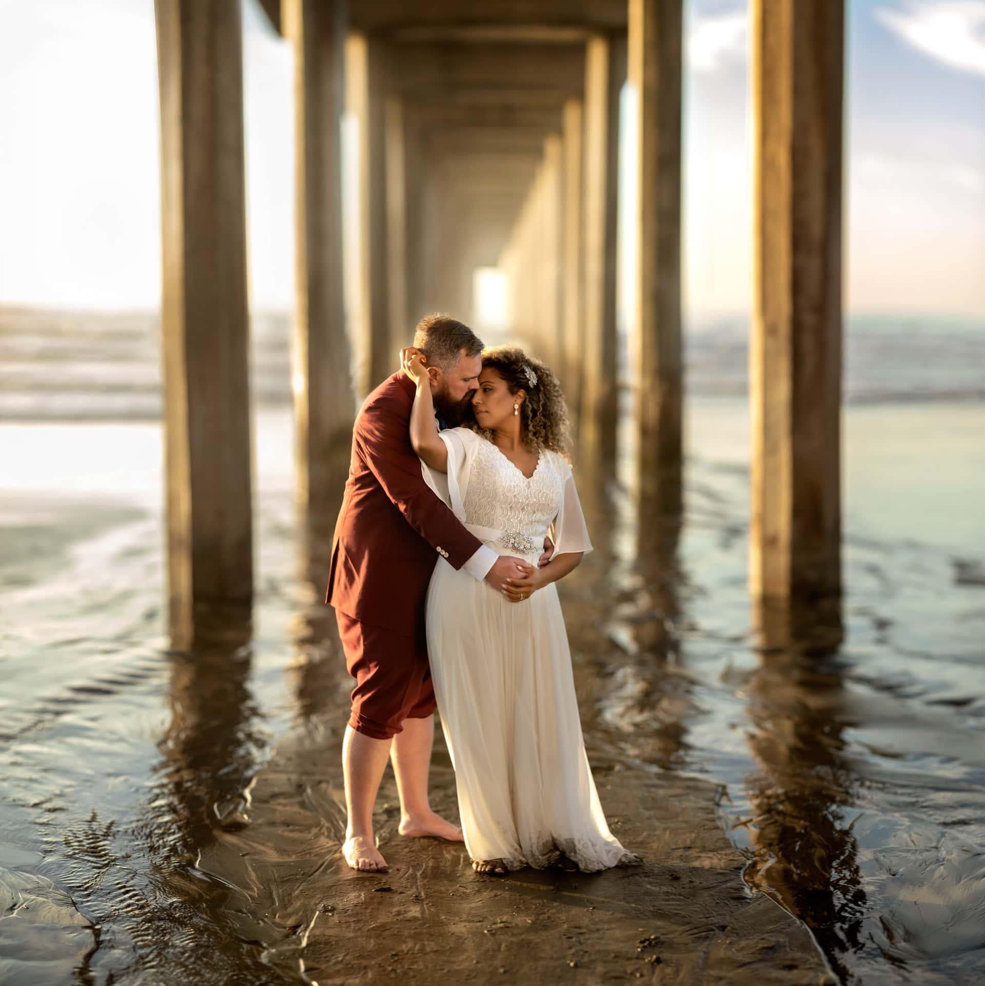 Gerusa and Eric under Scripps Pier Beach Wedding