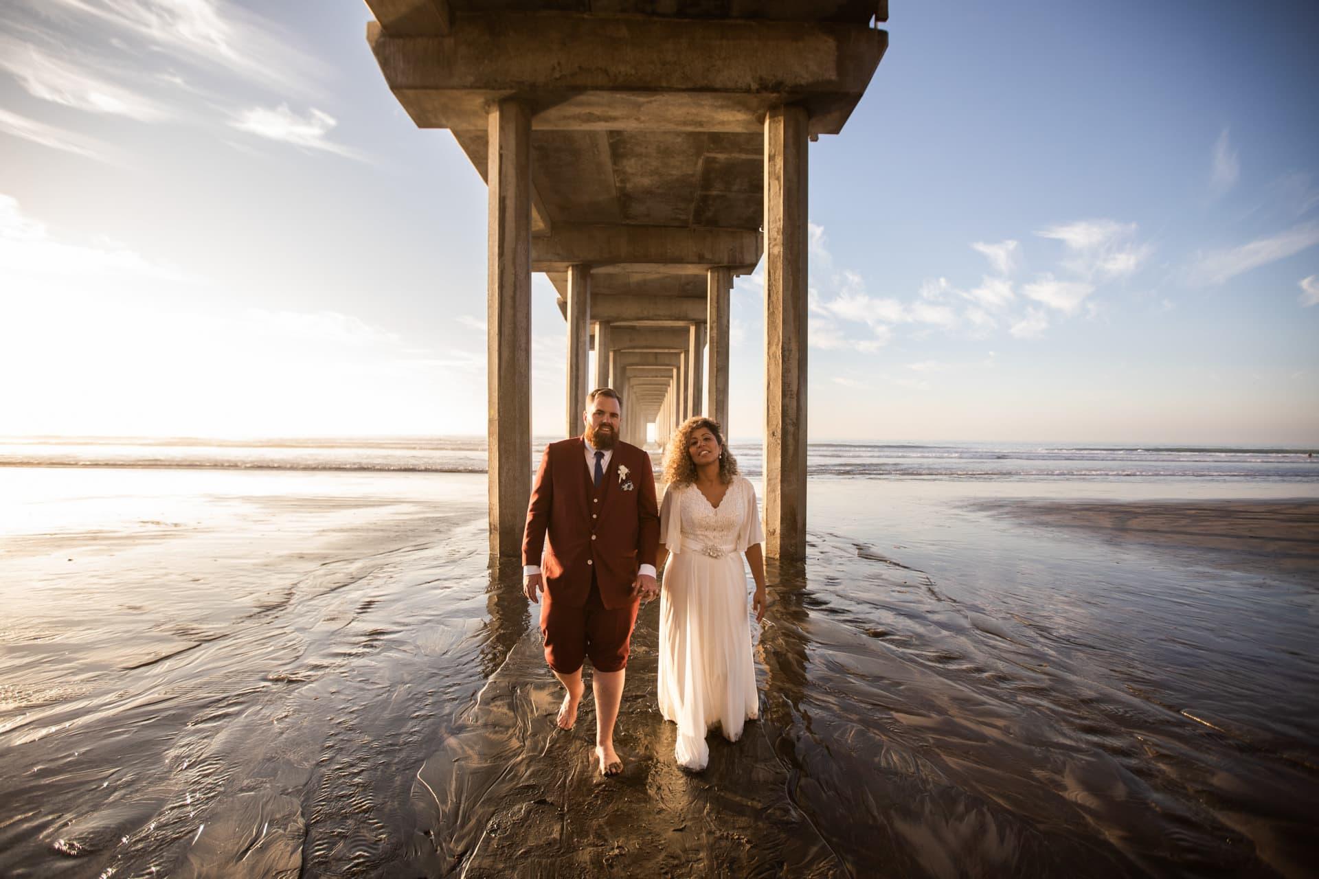 Gerusa and Eric Walking Under Scripps Pier Beach Wedding