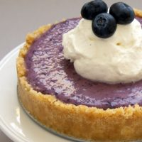 No-Bake Blueberry Cheesecake topped with sweetened whipped cream and blueberries