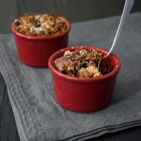 Dark Chocolate Bourbon Bread Puddings in red ramekins on a dark gray surface