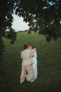 bride and groom kissing under tree