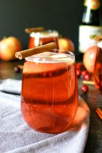 one cranberry apple cider mimosa with a cinnamon stick garnish
