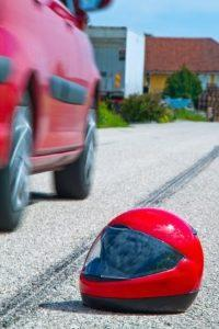 Motorcycle helmet next to skid marks on a road and a car