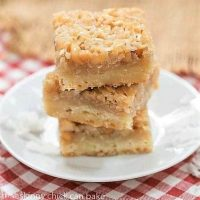 Coconut Macadamia Nut Bars on a white ceramic plate on a checkered napkin