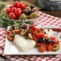Sea Bass with Tomatoes, Olives and Capers on small square plate with fork