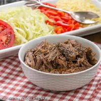 Slow Cooker Beef Barbacoa shredded in front of a white tray of toppings