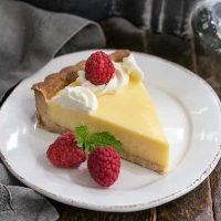 Slice of Creamy Lemon Tart on a white dessert plate