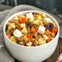 Mediterranean French Lentil Salad in a white bowl with red handled spoon