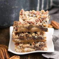 Toffee Caramel Magic Cookie Bars stacked on a rippled white plate