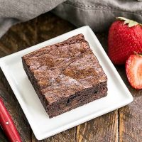 One fudgy sheet pan brownie on a square white plate