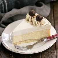 Slice of Tiramisu Cheesecake on a dessert plate with a red handled fork