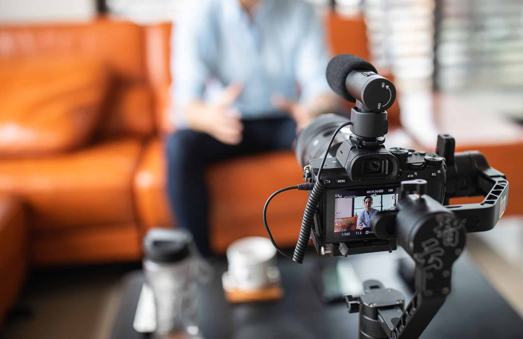 Video camera on tripod pointed at couch for interview video