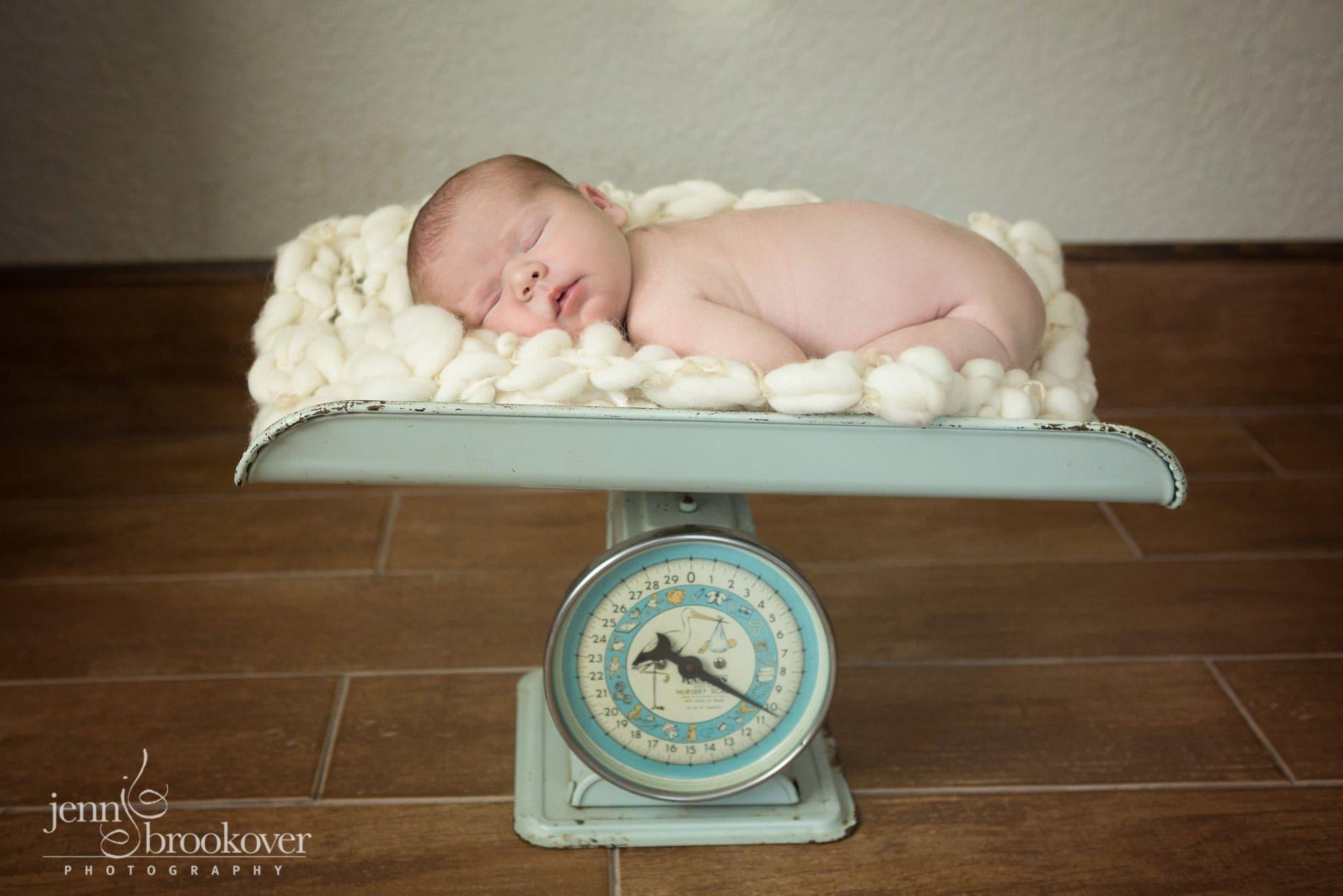 newborn asleep on vintage scale during newborn photo session