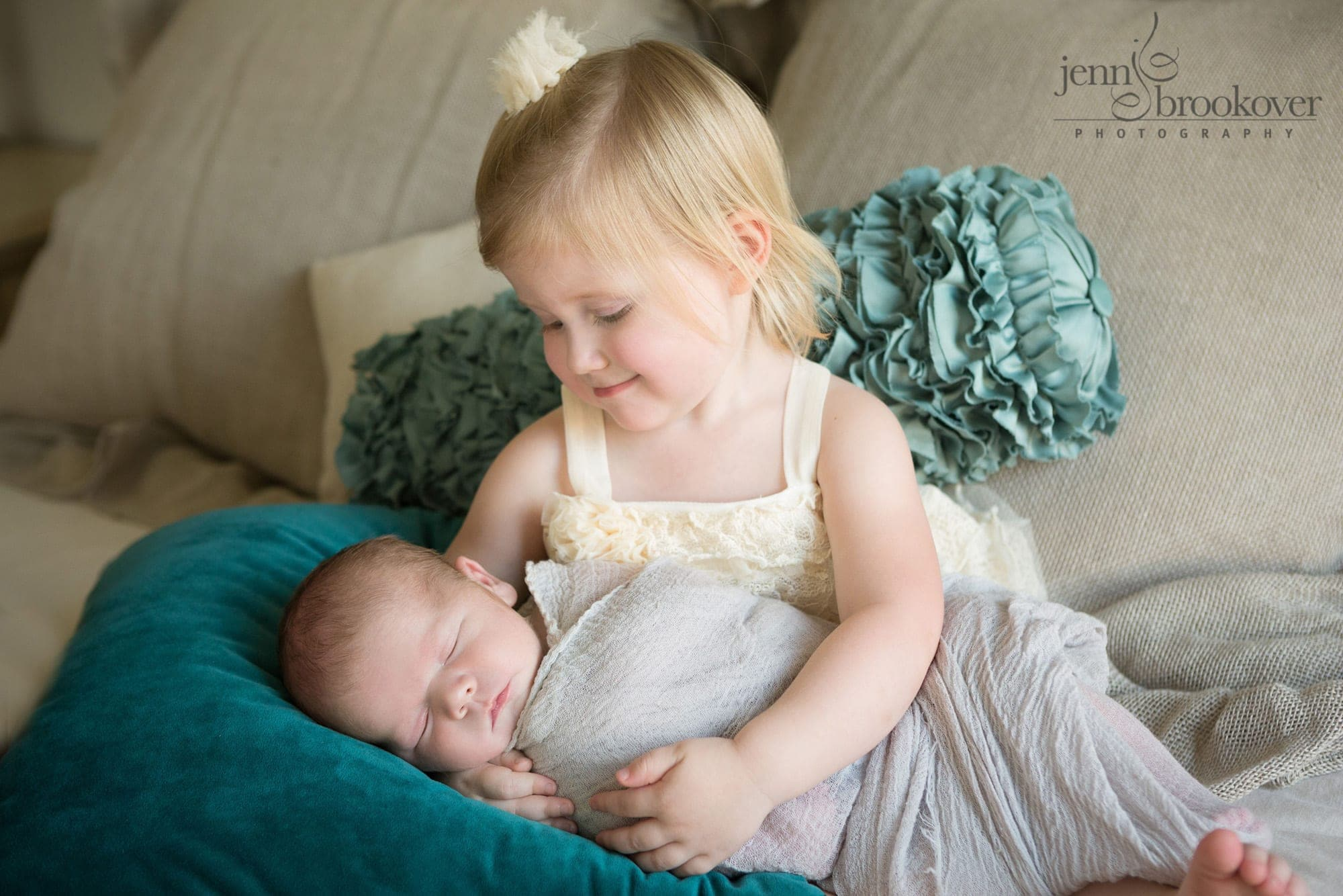 big sister smiling at newborn baby brother during lifestyle newborn session in San Antonio