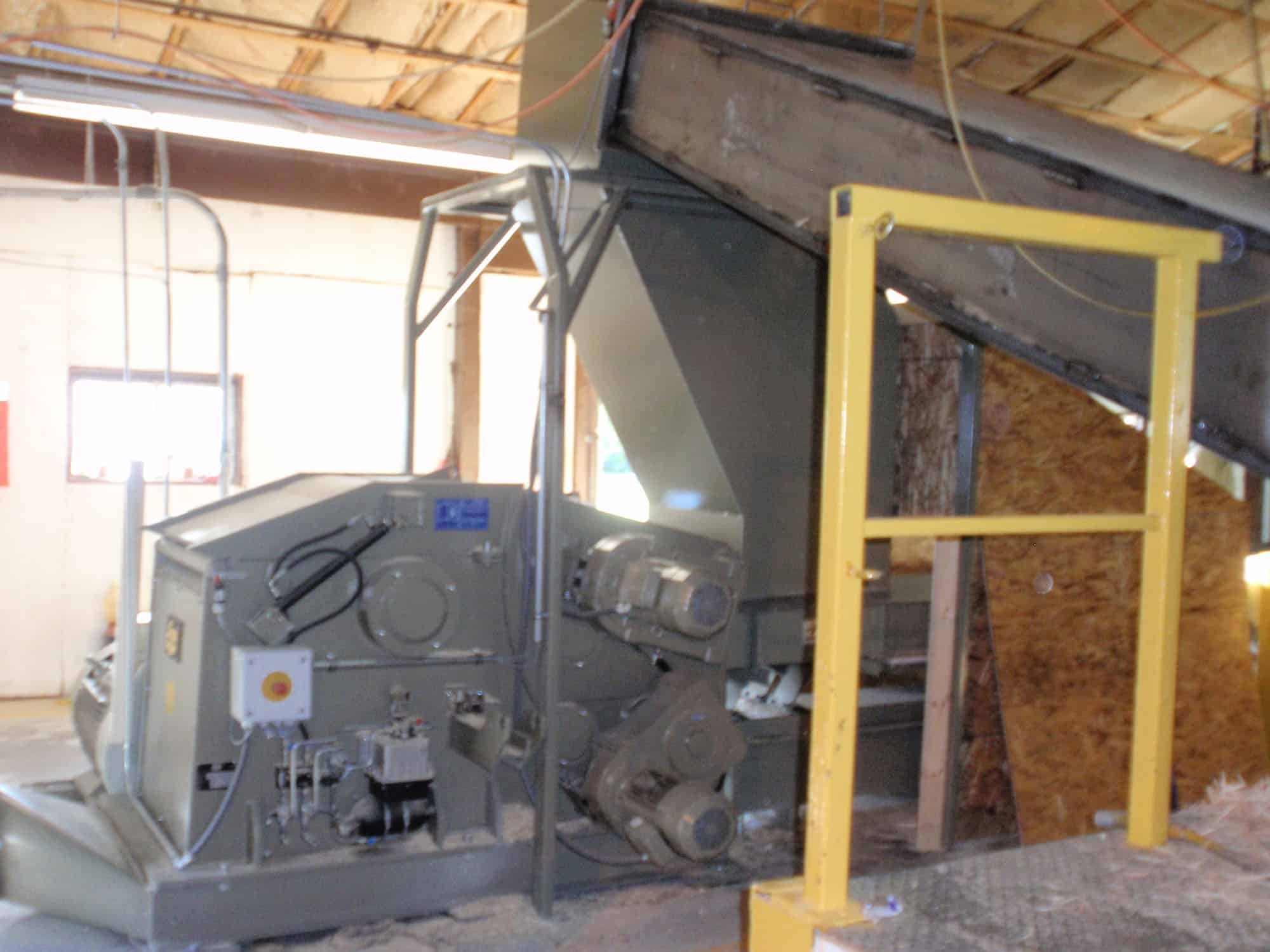 Wood chipper with band conveyor and feeding silo at production facilities