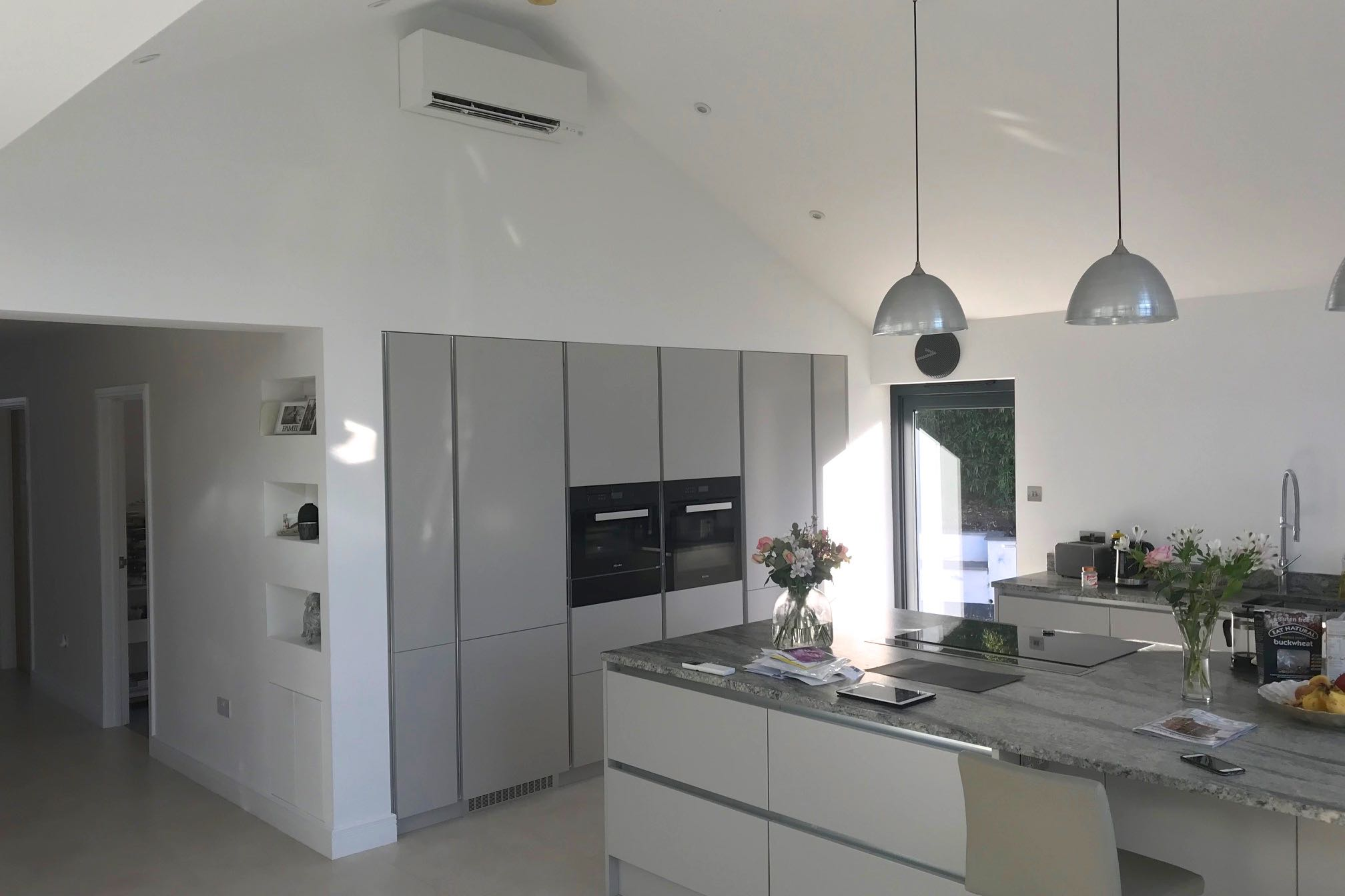 White wall mounted domestic air conditioning unit in open plan kitchen over fridge an oven units side view