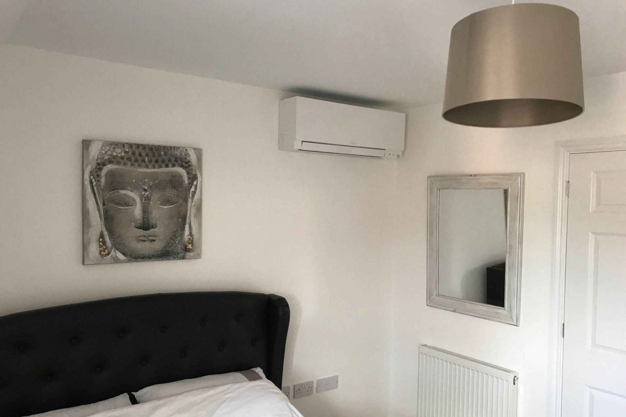 White mall counted mitsubishi domestic air conditioning unit in white and silver bedroom above bed