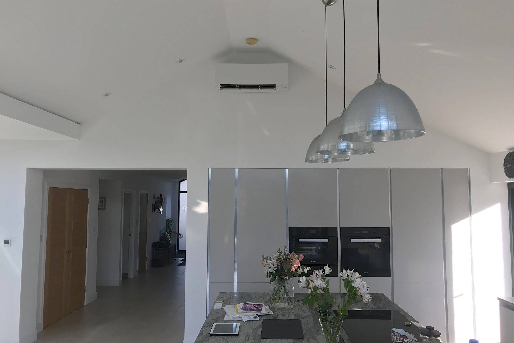 White wall mounted domestic air conditioning unit in open plan kitchen over fridge an oven units