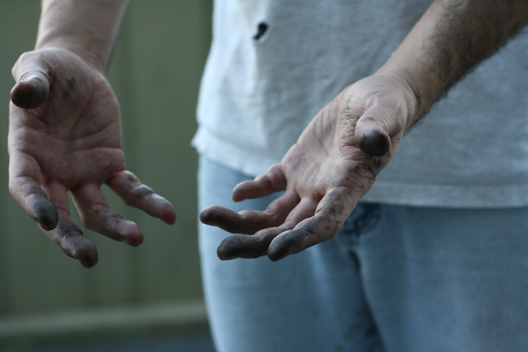 A man showing his greasy hands after working on a bike