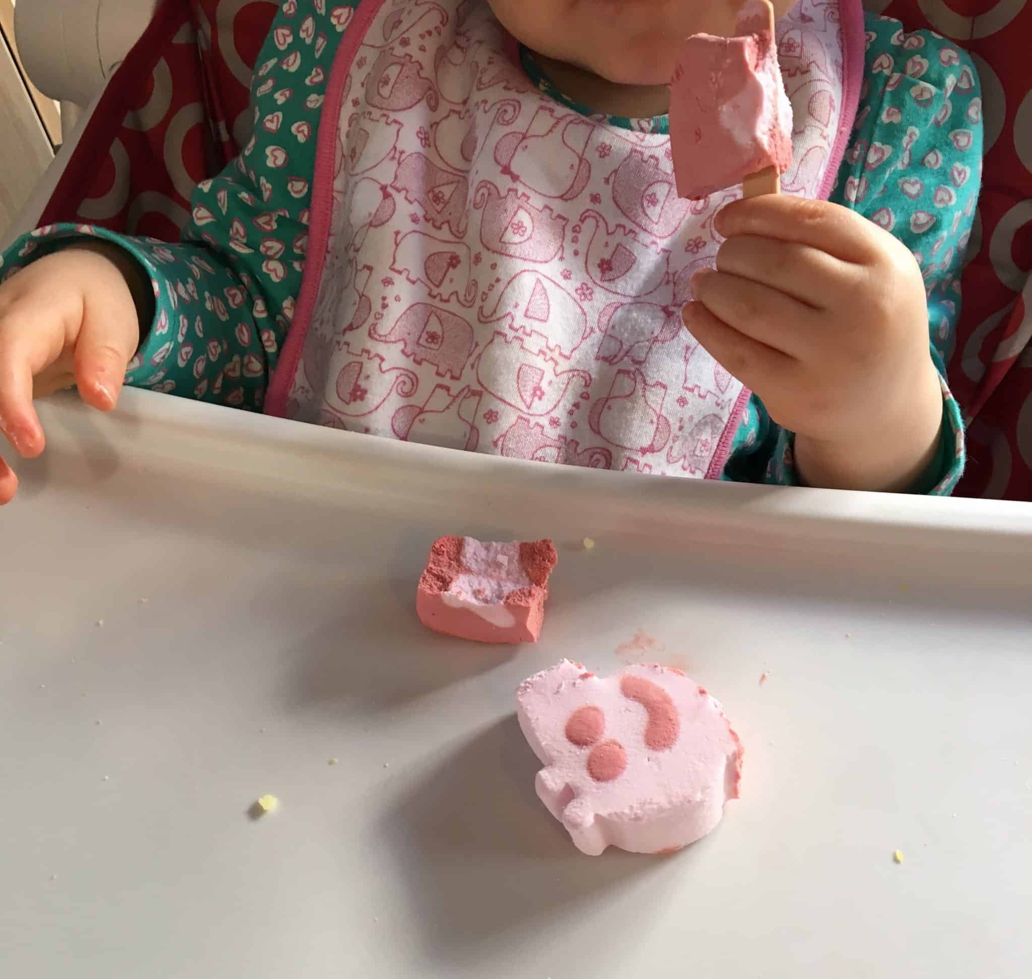 Baby girl eating peppa pig ice cream lollies