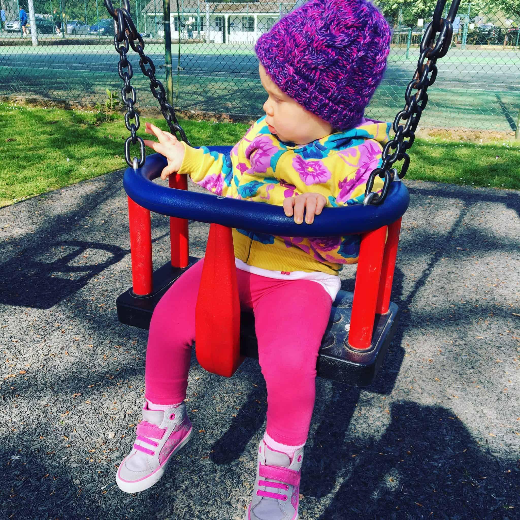 Baby girl on the baby swing at the park