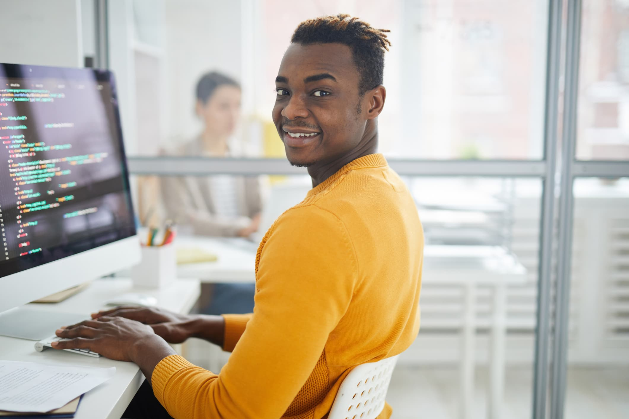 Smiling handsome young black programmer in yellow sweater sitting at desk and looking at camera while writing script for website in office